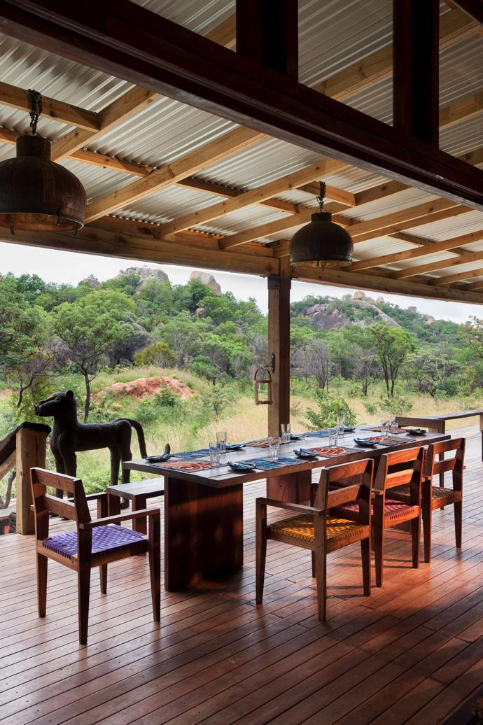 On the raised patio, a dining table and chairs from Homewood offer a perfect view over the veld. Thependant lights are from Amatuli.