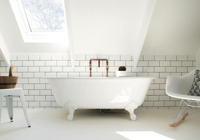 A skylight in the upstairs bathroom turns bath time into chill time in a vintage-style bath by MacNeil. The exposed copper pipes and metro tiles add to the retro feel. The stool is from Tolix and the Eames RAR rocker from Herman Miller.