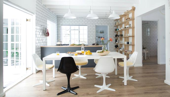 Hendré designed the main dining area and open-plan kitchen with its solid ash top. The ash hanging shelves were custom-made by James Mudge, and the table and tulip chairs are from Habitat in London. The wall tiles are by Kenzan.
