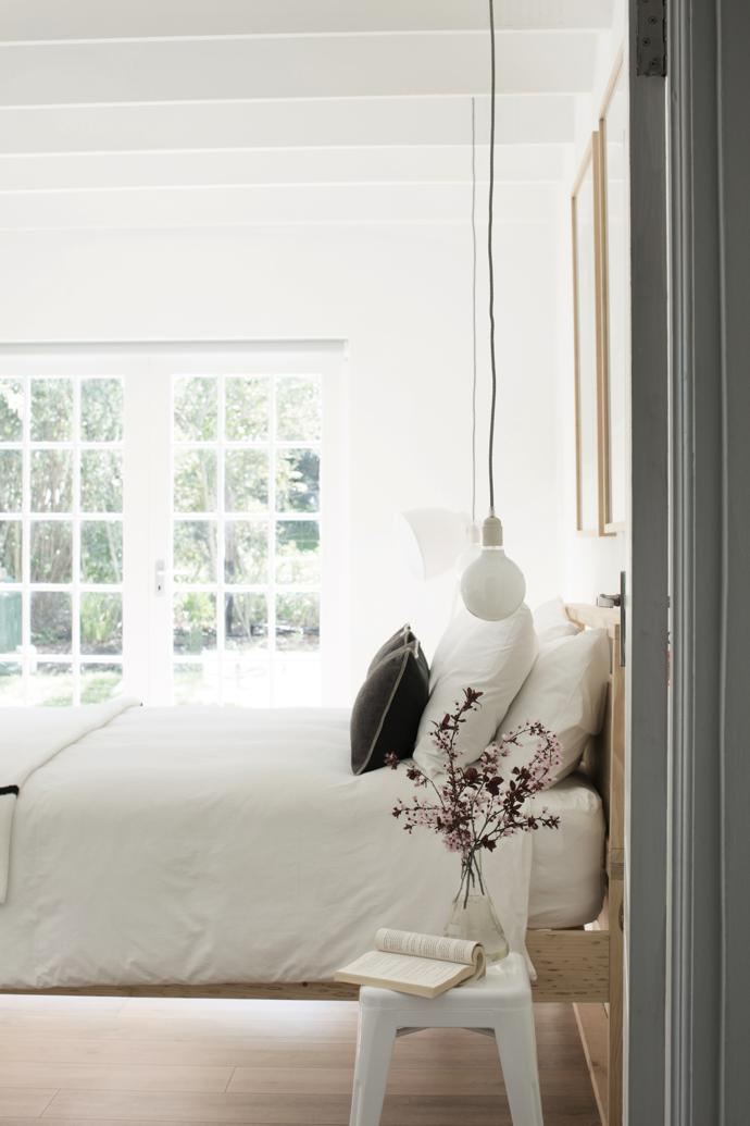 Keeping it white and simple in the main bedroom, where a custom-designed and locally made raw pine bed is the main feature. The floor lamp is from Weylandts. The French doors lead to the pool andgarden.