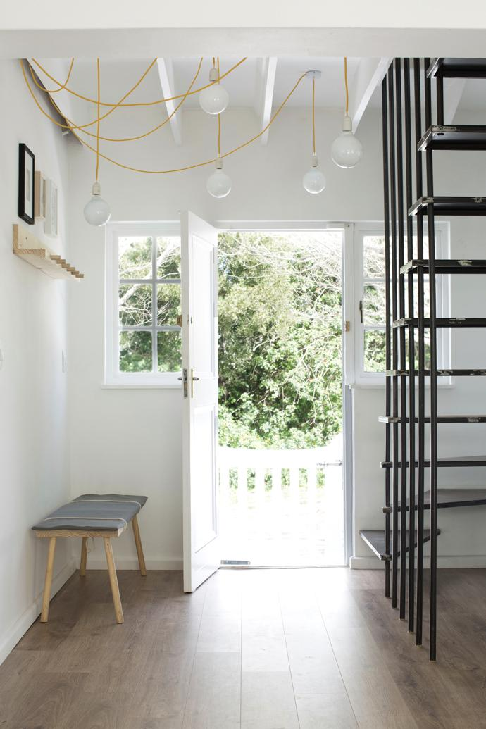 The entrance was redesigned to accommodate theraw steel staircase, designed by Hendré, and features pendant lamps from Hoi P'loy and acustom-made bench.