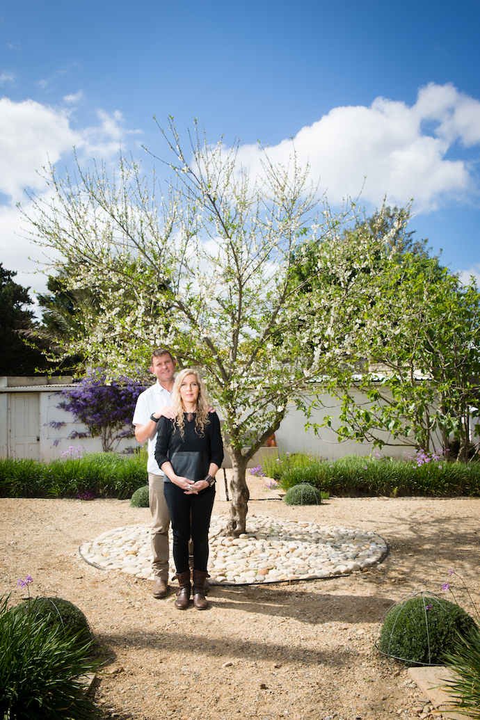 Wouter and Illze in front of a blossoming peach tree in the herb and vegetable garden Illze designed. In the foreground are two of four shaped westringeas.