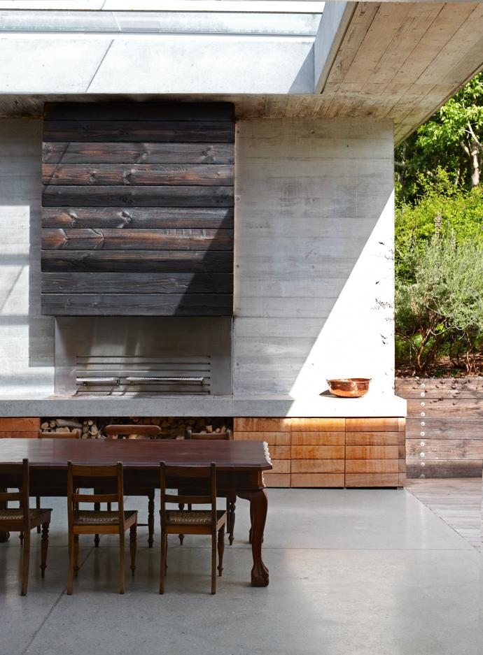 Heightening the play of inside/ outside is the use of a ball- and-claw imbuia dining table in the courtyard, where the family braais. Breaking with the wooden decking, the courtyard is  finished in polished concrete for ease of cleaning.