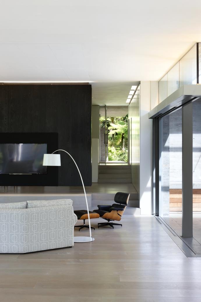 Here, one can clearly see the ground floor plane as a series of platforms that de ne di erent spaces within the larger volume. A  amed-cedar unit houses the TV on one side and the audiovisual and electronic equipment in the study on the other side.