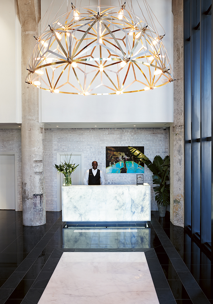 The bold, beautiful Tesla chandelier by Haldane Martin in the hotel foyer makes a dramatic statement. Porter Williams Inayor is at his post behind the counter.