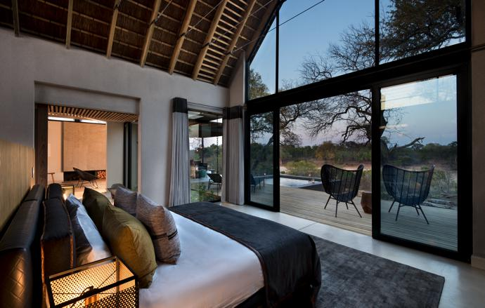 Huge glass sliding doors connect a bedroom to the outside.