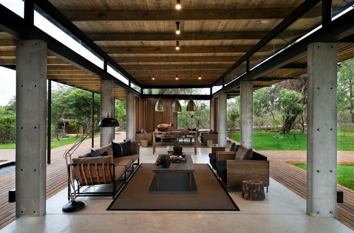 Generous timber overhangs protect the reception lounge from rain and direct sun, but the absence of partitions brings a very elemental connection to the bush. The use of concrete, wood and considered furniture contribute to the lodge's contemporary aesthetic. The larger furniture pieces were designed by Meg and custom-made by The Noble Collective for MT Spaces. The pendant lights are from Amatuli, and the floor lamp is from Sixth Floor at Superbalist.