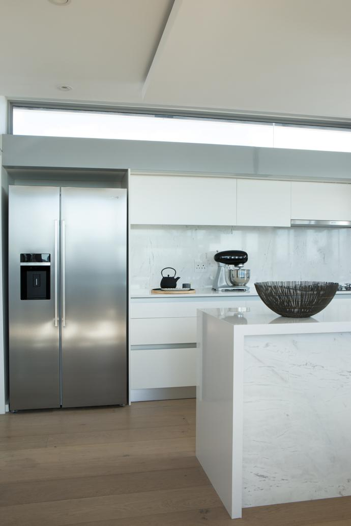 In the kitchen, white marble off sets the matte black taps. It features a full suite of Smeg appliances, including the fridge, washing machine, tumble dryer, dishwasher and Dolce Stil Novo oven and hob range.