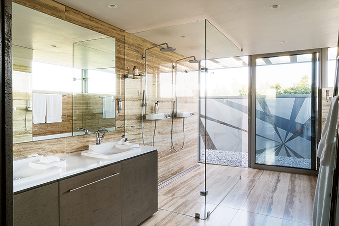The bathroom, designed by Julia, takes the form of a stone box, featuring oversized travertine tiles and sanitaryware from the Axor Bouroullec collection at Hansgrohe. Frameless glass and generous mirrors give this sanctuary a sense of space.