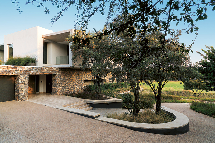 """The driveway, flanked by ornamental grasses, winds up to one of the stone-clad """"bookends"""" of the house."""