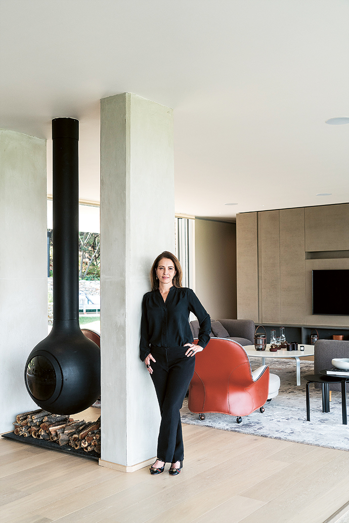 Interior designer Julia Day, standing next to a Focus Bathyscafocus, a suspended rotating fireplace that the homeowner refers to as functional art.