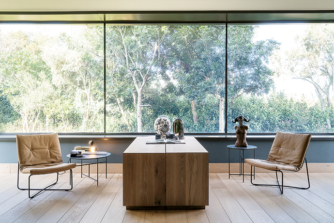 In the tranquil office, a view of the garden is bookended by a pair of LC03 chairs by Maarten van Severen and Fabian Schwaerzler.