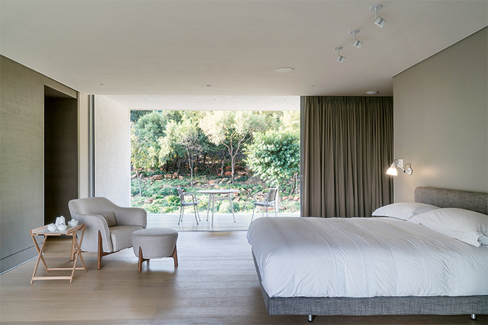 The main bedroom is a spartan, calm space, with a balcony that overlooks the estate's nature reserve. A Pilotis armchair and ottoman by Philippe Nigro are paired with a Vico Magistretti Sleeping Car bed, upholstered in a slubby linen to add texture.