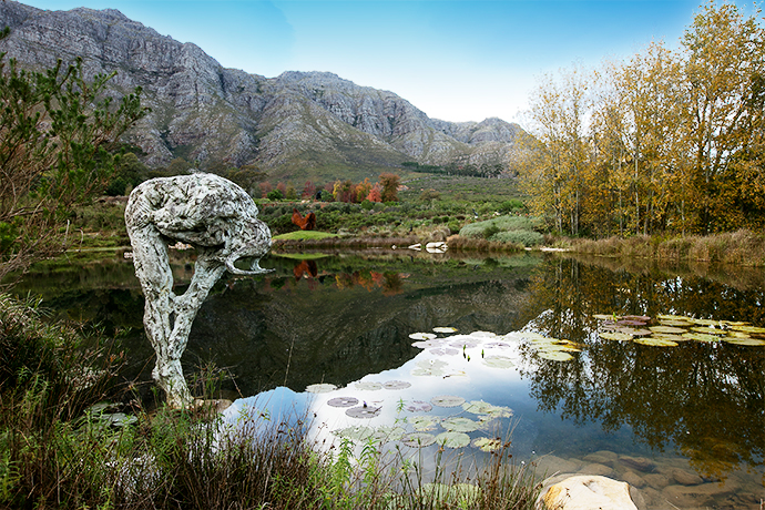 """The view of the lake Dylan shaped, with Stellenbosch Mountain as backdrop. The face of the stooping Male Trans-Figure III is obscured. """"It puts a focus on the body as a vehicle for expression as opposed to the face,"""" says Dylan."""