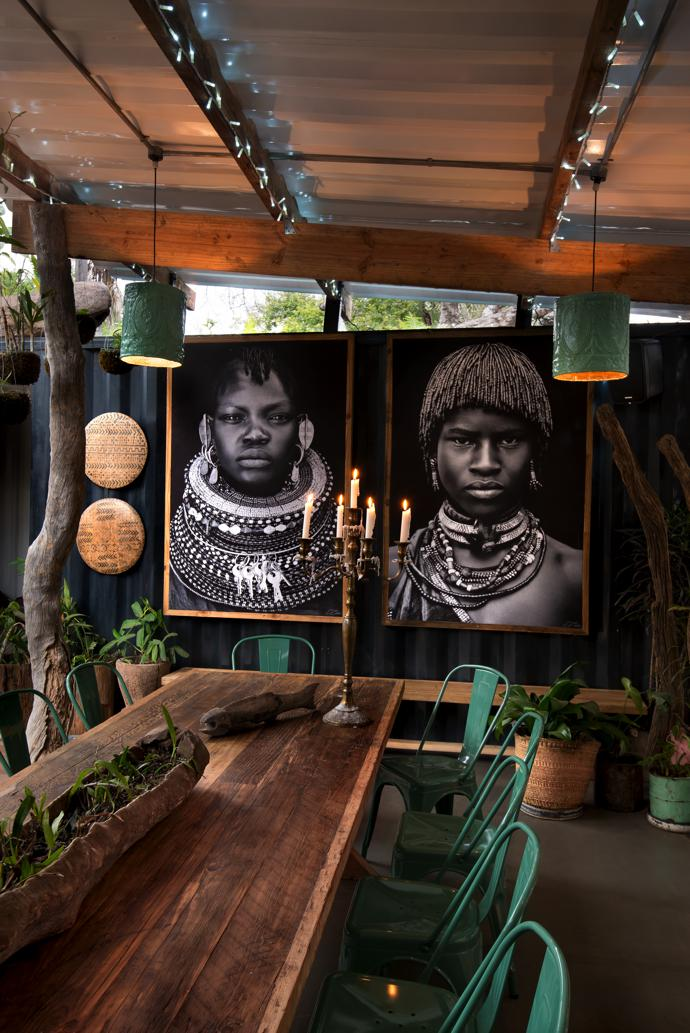 The table and chairs in this private dining area were sourced from Amatuli. Portraits by David Ballam are part of the photographer's Turkana series. The hanging shields are from Cameroon and the stock feeder on the table is from the Zambezi valley.