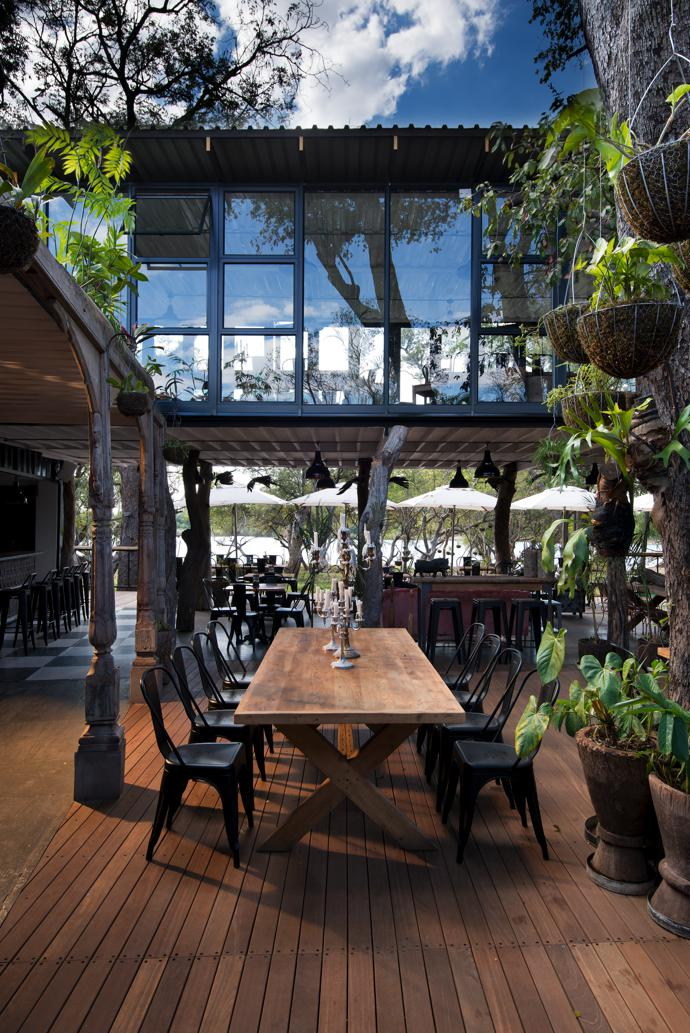 A timber deck suspended between the two sides of the building creates a courtyard featuring a multitude of plants collected by a Vic Falls trader from all over Zimbabwe, from Chimanimani in the Eastern Highlands to the Matopo Hills.