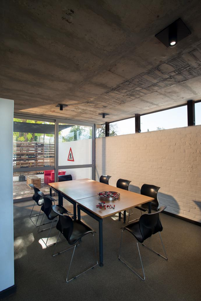 """Above the table in the meeting area, the ceiling features what Pieter calls their upside-down carpet. While the concrete was wet, he and his team pressed off cuts from a model they'd built for the Pretoria BRT station at Church Square into it (after first spraying it with cooking spray so the pieces would come away easily) and this """"negative"""" of the model left behind a relief as a reminder of their work."""