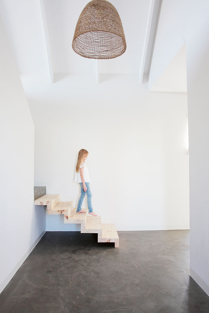 Allegra Swart, photographer Henrique's daughter, walks down the stairs that lead to the sea facing bedroom located at the front of one of the wings.