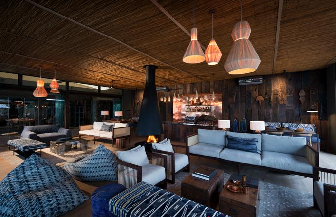 Railway-sleeper cladding on the walls and copper cladding on the cocktail bar add warmth to the main lounge, where oversized bean bags contribute to the casual chic ambience. The pendant lamps are from WireWorld, and the sofa and armchair were designed by Fox Browne Creative and made by Hark Design.