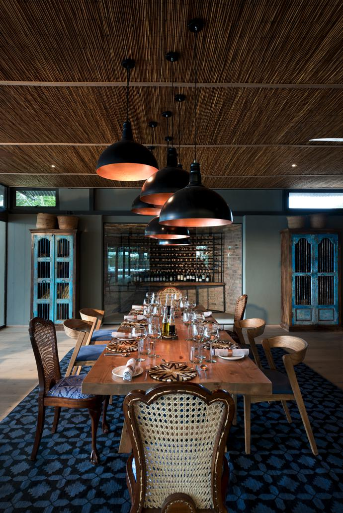 Fox Browne Creative's effortlessly chic mix of antique and Mid-century Scandi dining chairs – from antiques shops and Mezzanine – combined with dramatic copper pendant lamps from Sutherlands Home Furnishing creates a cosy focal point around the table. The curved wall of the temperature controlled wine room mirrors the curved walls of traditional Lozi buildings. Flanking the glass doors to the wine room are two cabinets from Amatuli.