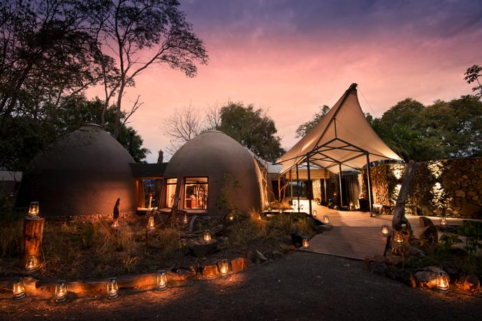 The canopy at the entrance to the lodge – by Tenthouse Structures – mimics the canopies over the rooms. The two beehive-shaped buildings on the left, inspired by traditional dwellings of the Lozi people, house the shop and library. They each feature a skylight in the apex of the dome that allows a beam of sunlight to illuminate the interior. The thick walls help to keep the interiors cool