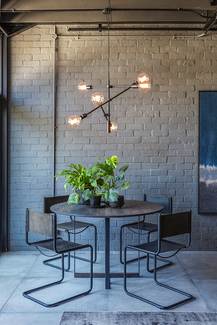 An Acrobatic pendant, which epitomises the chic industrial inner-city loft aesthetic, is suspended above a Gamma round dining table in ebony, matched with four Swing leather-and-iron dining chairs.
