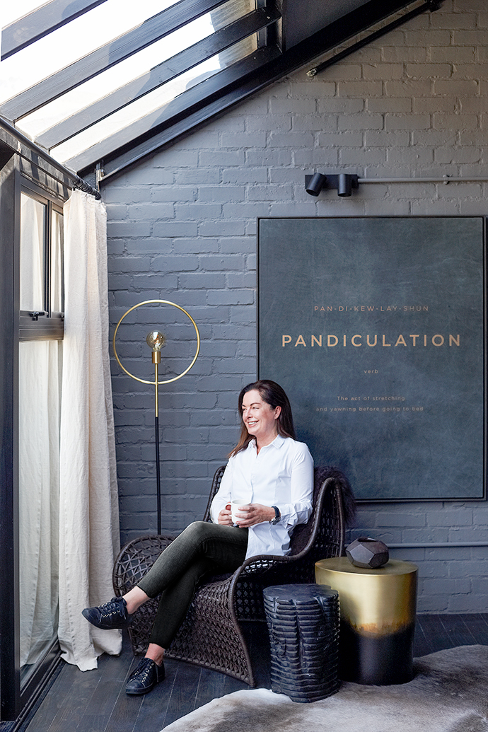 Kim Smith sits in a Louise chair, whose weaves match with the Garis stool beside it, which in turn blends into the oval shaded-gold stool. The colour of the stool also triangulates subtly with the Hoop floor lamp and leather wall art named Pandiculation (yawning and stretching when you wake).