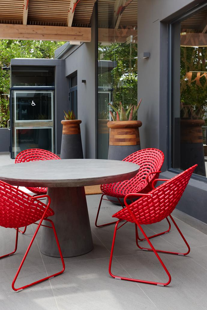 Zulu Mama café chairs, another classic Haldane Martin design, and Soma planters by Laurie Wiid van Heerden for Indigenus at the entrance to the building.