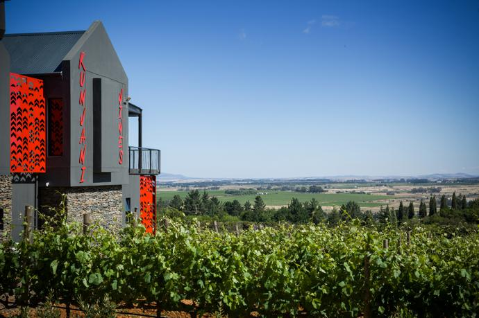 Not your traditional Cape Dutch style building! The bright red of the screens, with their chevron like shapes that evoke traditional West African hut decorations, and the bold signage contrast deliberately with the green of the landscape.