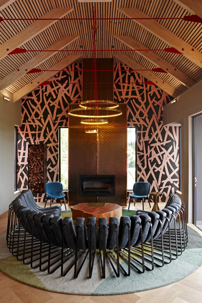 The fireplace surround is made of a quilted aluminium that has been anodised to look like bronze, with copper strips to cover the joints. In front of it is a Haldane Martin Songololo sofa.