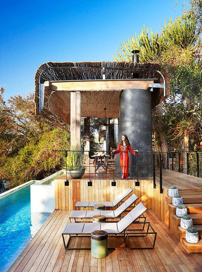 The terrace's nest-like structure has architectural echoes of the other buildings. The steel frames of the Mobelli loungers mirror the railing. They are paired with ceramic side tables by Cécile & Boyd. Succulents in blue-and-white vases from Cécile & Boyd climb the stairs. Model San-Mari Pietersen wears a Tribal Kaftan, designed by Jane Letschert from Tribe.Luxe, available at Singita Gallery & Boutique.