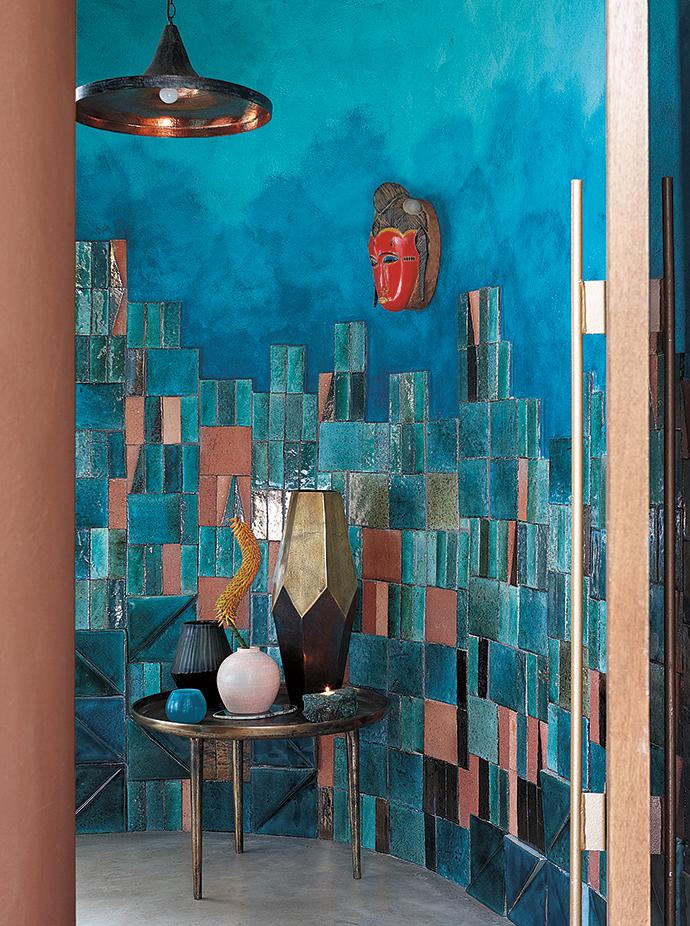 The Cécile & Boyd team used handmade clay tiles by Southern Art Ceramics to create a pattern in the entrance to the guest toilet. They are juxtaposed with a vibrantly painted wall by artist Sarah Pratt. Glass and brass vessels by Cécile & Boyd stand on a brass table by La Grange Interiors.