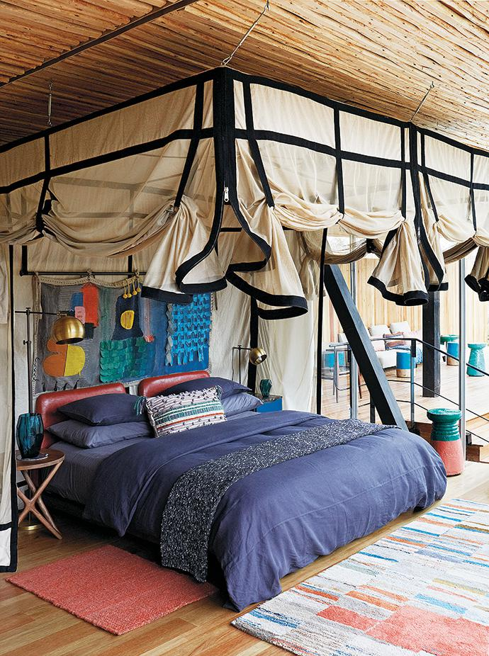 The bed's striking leather headboard, below a wall hanging by African Sketchbook, was custom-made by Wunders. Kiwinet created the mosquito nets.