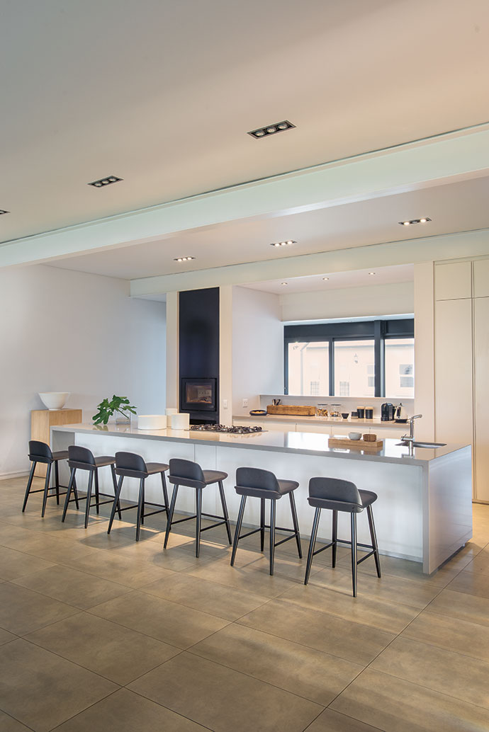 The kitchen, which was opened up to the lounge, features bar stools from Chair Crazy and Technistone countertops.