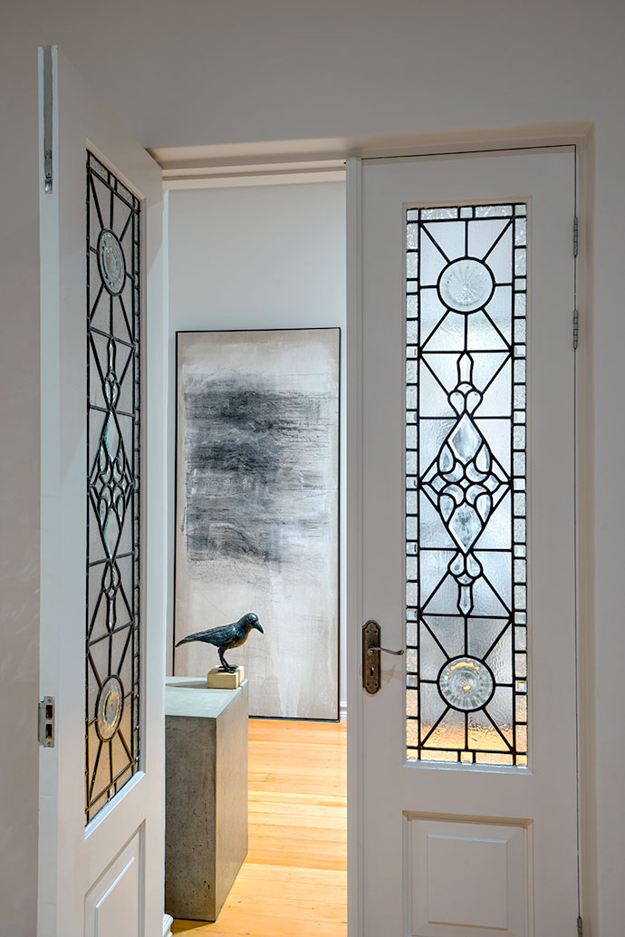 Looking through the doorway with original leaded-glass doors, the entrance hall features a painting by artist Lynette ten Krooden and a crow sculpture by Rossouw van der Walt.