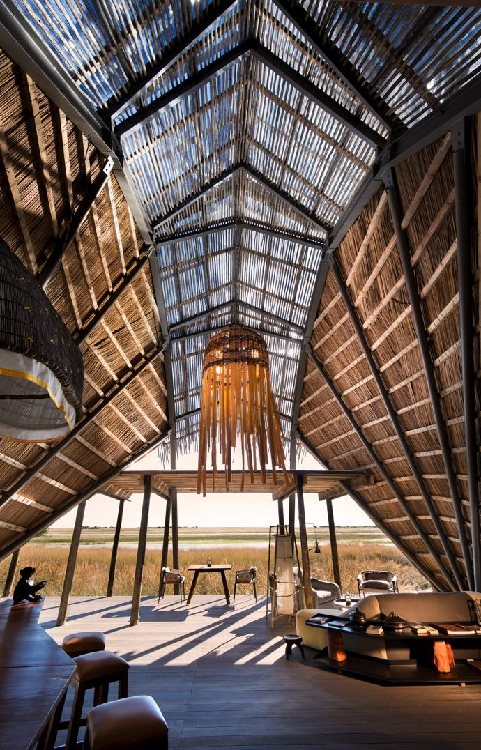 The shape of the main lounge is inspired by the dragonflies that flit around the floodplain. Overlapping roof planes and the transparent membranous ceiling mimic their finely veined wings, and the bar counter and sofas pick up on these faceted lines. The design of the big pendant light is inspired by traditional Lozi fishing baskets.