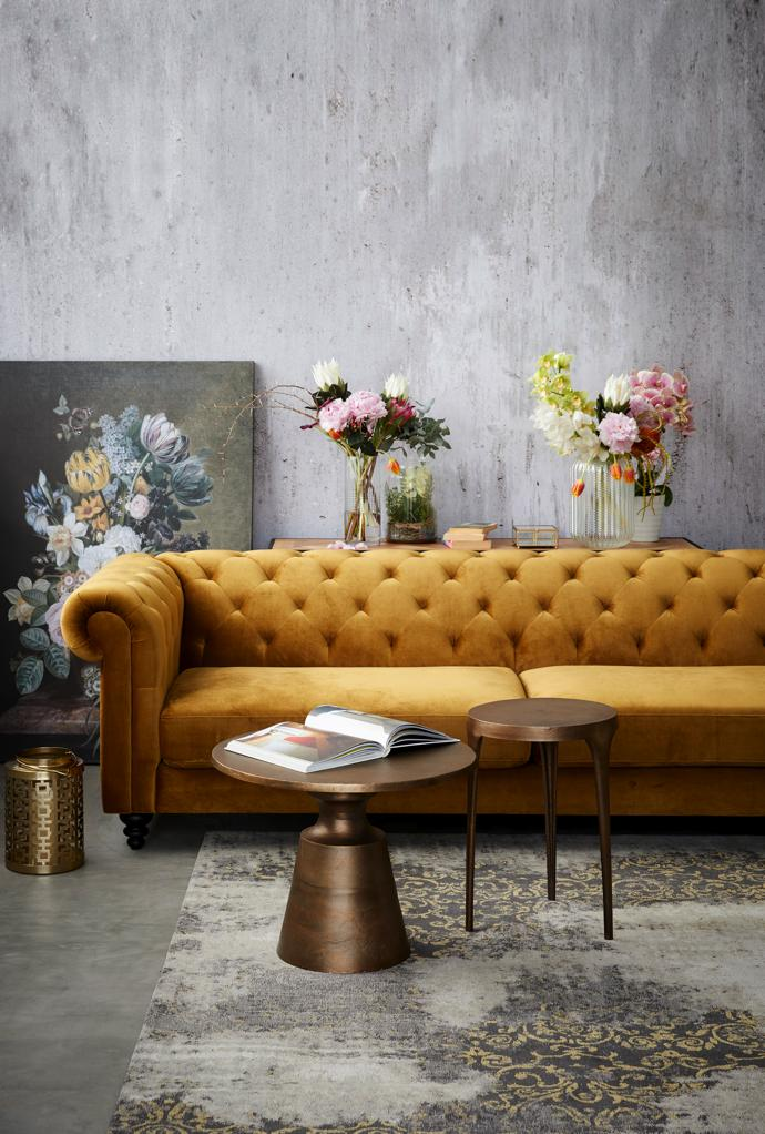 Flourish: Bronze Velvet Chelsey 3 Seater, Brass Nova Antique Side Table, Brass Cleo Antique Side Table, Yellow Damask Faded Cotton Carpet, Gold Iron Hurricane Deco Candle Holder.