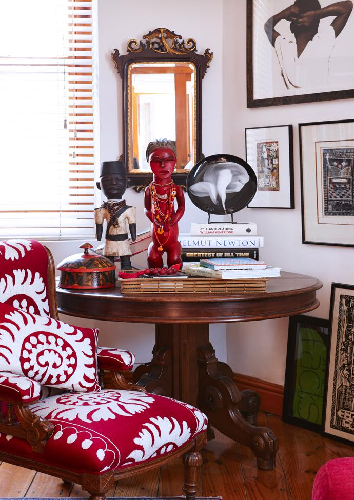 Art fills the walls and floor of Juditha's apartment. On a table that once stood in her parents' home are favourite statuettes and a pile of books, which serves as a pedestal for a Robert Mapplethorpe Calla Lily plate. The chair is upholstered in Suzani tribal textile from Uzbekistan.