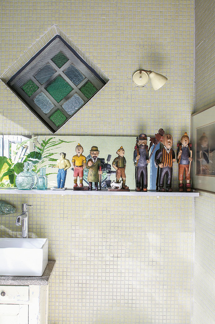 The hand-crafted Tintin collection in the bathroom was a find at Milnerton Flea Market, and the wall-mounted yellow desk lamp was discovered at a brocante (flea market) in Charroux, France.