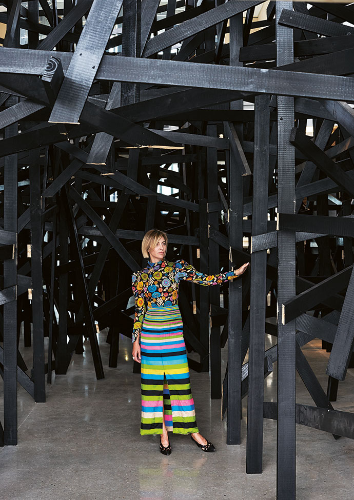 Natalie stands underneath the large-scale installation Structural Response III by Serge Alain Nitegeka in the atrium.