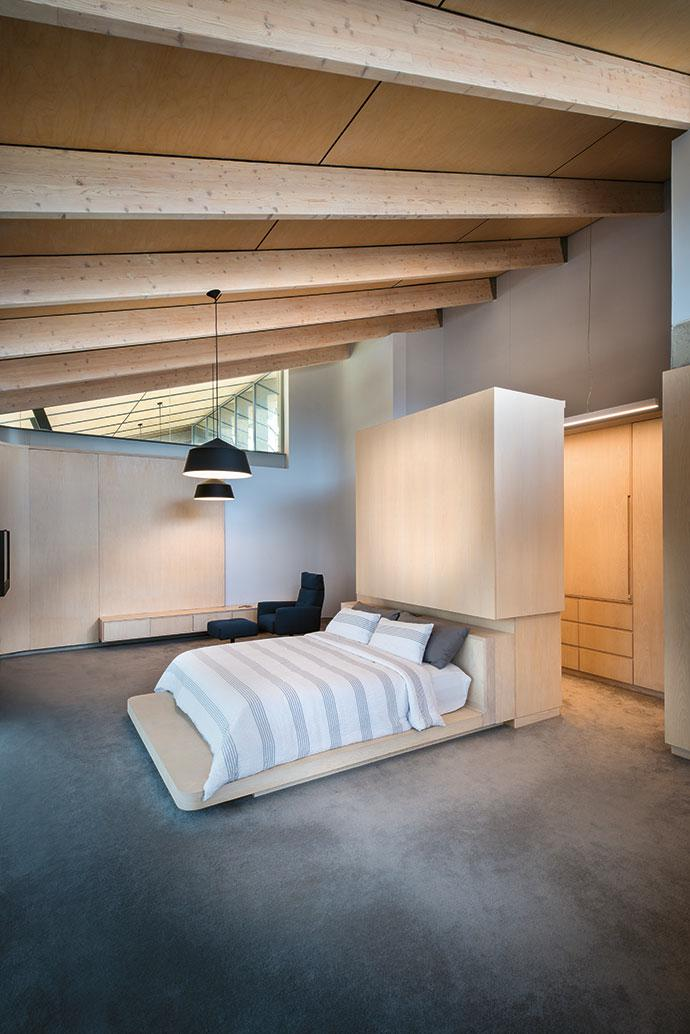 In the master bedroom, Scandinavian and Japanese influences are evident in the warm minimalism of the furnishings, blending with the architecture to create a calming integrated design. The armchair is by Rolf Benz.