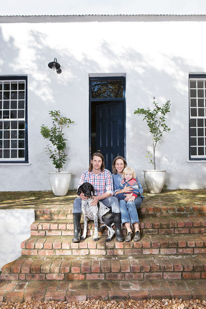 Alex and Sumari with their youngest son Georgie and their dog Holly on the steps outside their home.