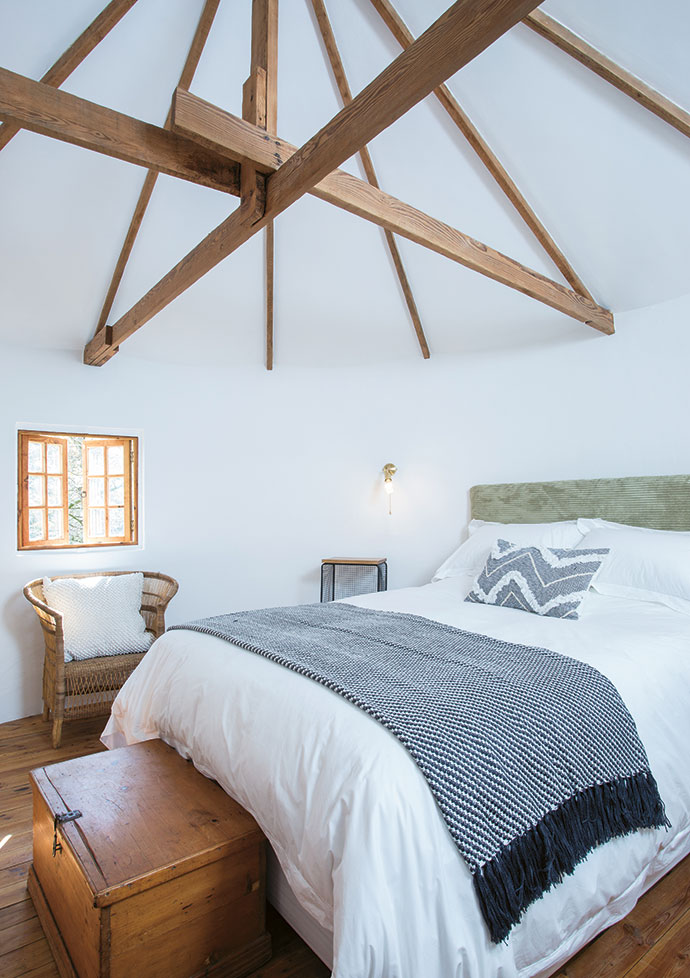 A Sealy queen-size bed dominates the space in the bedroom upstairs. The roof trusses were made from a stack of Oregan pine that the couple had amassed before the renovation.