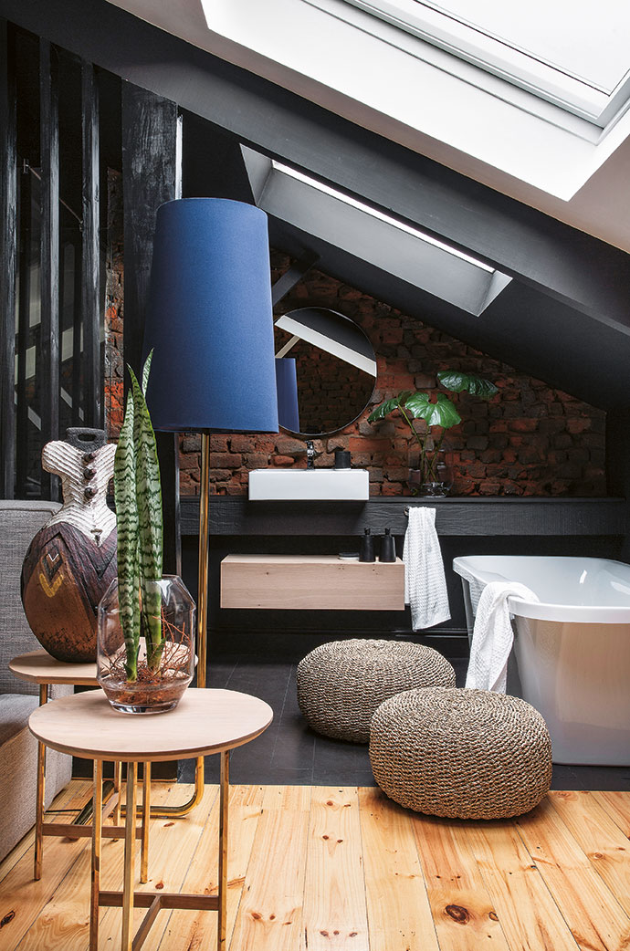 In the main en-suite bathroom, a timber roof truss is cleverly used as a shelf. Above the freestanding bath are two large skylights.