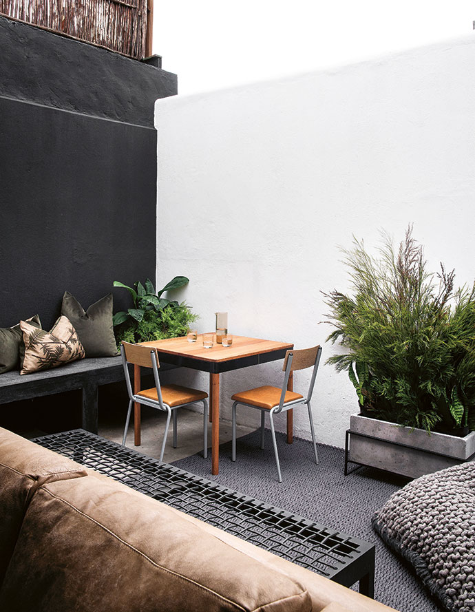 The back of the property features a private courtyard with a built-in bench. An outdoor dining setting by Pedersen + Lennard is complemented by a riempie bench by James Mudge. An outdoor rug from Weylandts adds a soft touch on the raw concrete floor.