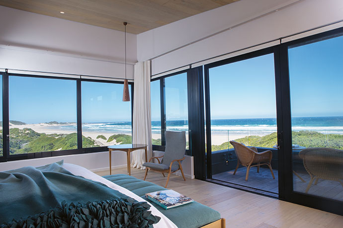 The colours in the east-facing master bedroom were chosen to pick up the views: the crimson of the sunrise and aquas of the ocean. The bed was centred in the view, and Andrew Dominic Furniture created the assymetrical side tables. The reading lights are from Gigi's Design House (as are all the lamps throughout). A Joburg pendant by David Krynauw hangs above a side table by Casamento and Signature chair by Frits Henningsen. The outdoor chairs are from Tonic.