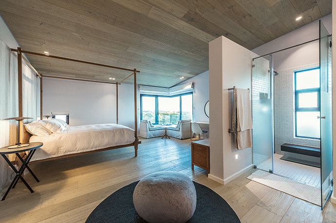 James Mudge created the four-poster, Casamento the L-shaped sofa, Gregor Jenkin the side tables and Ronel Jordaan the Pebble cushion on the circular wet rug by Fibre Design. A Philippe Starck chair stands in front of the dressing table below a Tonic mirror.