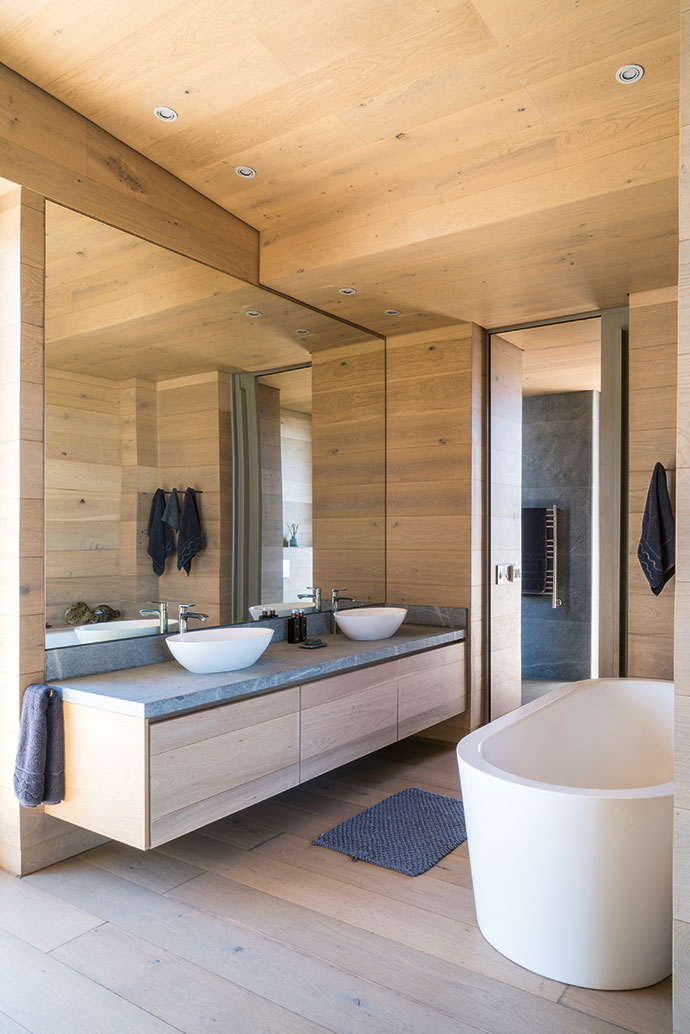 The main bathroom's large mirror extends the space considerably and reflects the interesting angles of the cladding and joinery.