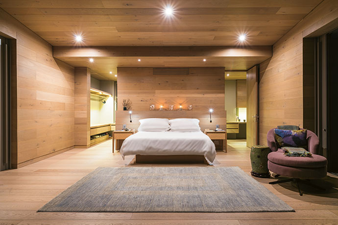 """The bed in the main bedroom has a cantilevered effect, which playfully echoes the house itself. Behind it are the dressing and study alcoves. The floating effect, says Johann, """"is from the way the surfaces meet each other. I prefer a shadow line where the surfaces meet, giving a floating effect."""""""