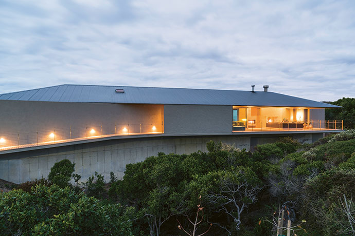 A view from the north showing the lit entrance gives a good idea of how the Floating Dune House got its name, as it hovers above the milkwood canopy. Note the corrugated iron roof – a signature Johann Slee reference to South African vernacular architecture.